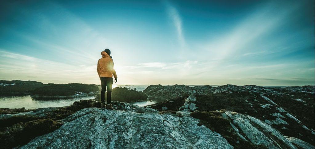 En kvinne som står å ser utover en norsk fjell landskap