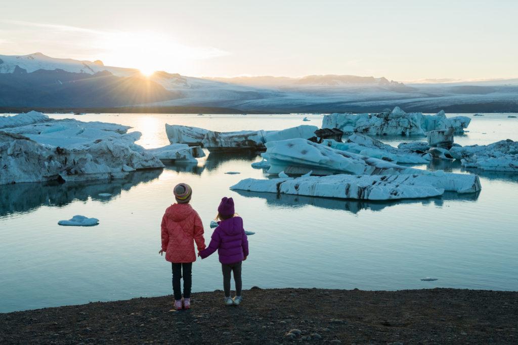 To barn som står og ser på is på havet som smelter.